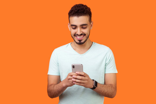 Portrait of cheerful brunette man with beard in white t-shirt using cellphone and smiling, reading good news message, enjoying mobile application. indoor studio shot isolated on orange background