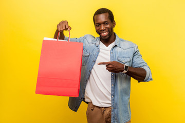 Portrait of enthusiastic happy male buyer with attractive toothy smile wearing denim casual clothes pointing at shopping bags, looking satisfied. indoor studio shot isolated on yellow background