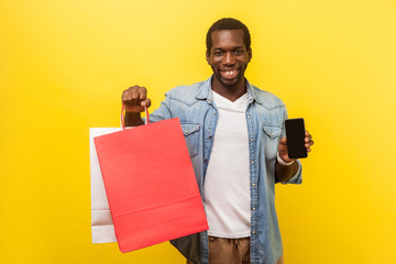 Online shopping and cashback. Portrait of positive man with attractive toothy smile in denim casual shirt holding packages and showing smartphone. indoor studio shot isolated on yellow background