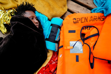 A migrant rests on board a NGO Proactiva Open Arms rescue boat in the central Mediterranean Sea