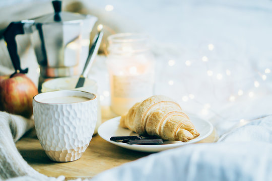 Cozy winter weekend breakfast, coffee and croissant on wooden tray