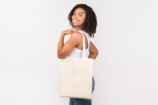 Black girl with blank eco sack on white background
