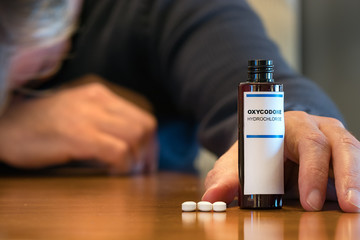 Prescription bottle with Oxycodone tablets on a table with a human hand next ot it