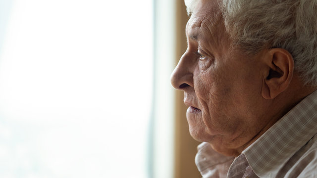 Pensive older man looking out of window, recollecting memories.