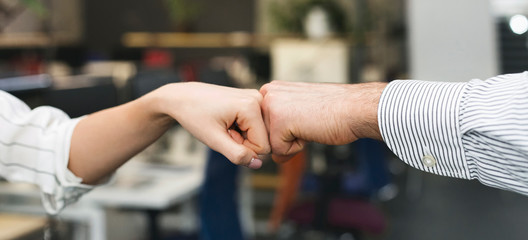Man and woman making fist bump gesture in office