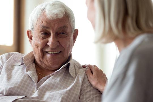 Smiling elder male patient communicating with nurse.