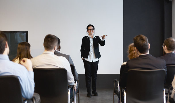 Business training. Female speaker giving lecture to audience