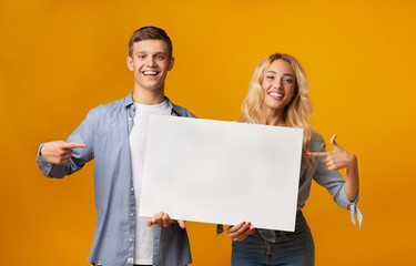 Young couple holding blank advertising board and pointing on it