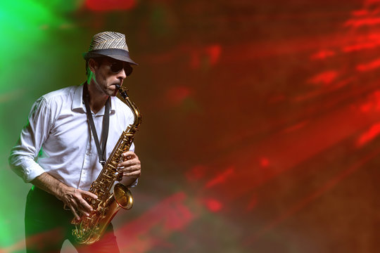 Man playing saxophone in a club with laserlights