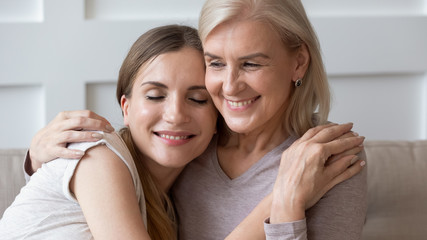 Peaceful smiling older retired mother embracing calm happy daughter.