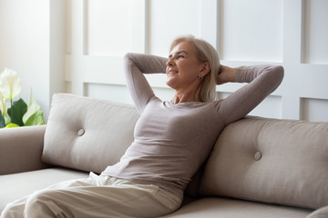 Fototapeta Happy middle aged retired woman relaxing on comfortable sofa. obraz
