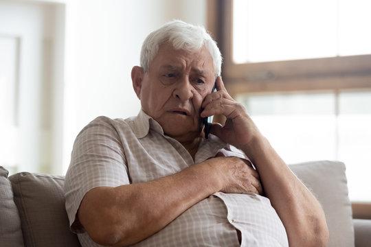 Worried older unhealthy man making emergency 911 call.