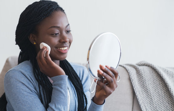 African woman looking in mirror and cleaning face with cotton pad