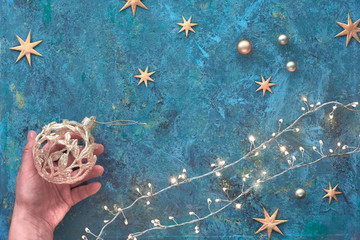 Christmas or New Year flat lay background on dark tile textured board. Top view flat lay on Xmas garland, golden baubles and stars. Hand holding ornate trinket. Merry Christmas and a Happy New Year!