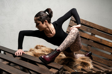Caucasian young beautiful model in black bodysuit, fashion tights with leopard print and burgundy demi season boots posing stretching indoors on a wooden pallet Wall mural