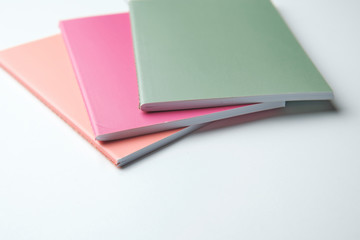green, pink and orange notebooks