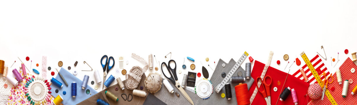 Panoramic view on sewing composition with threads, fabrics, scissors, buttons, needles and other sewing accessories on white background. Long banner, top view, copy space, flat lay, mock up