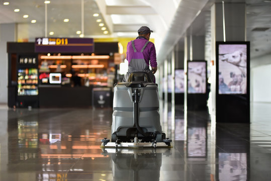 Man driving floor scrubber or floor cleaning device in airport