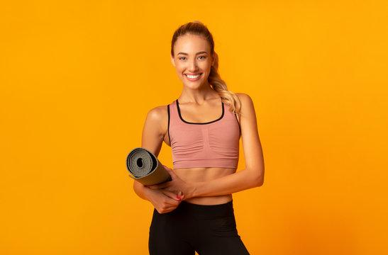 Girl Holding Fitness Mat Looking At Camera Standing, Studio Shot