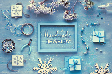 """Making handmade jewelry for friends as Winter holiday gifts. Flat lay on dark textured background, text """"Handmade jewelry"""". Creative diy craft hobby."""