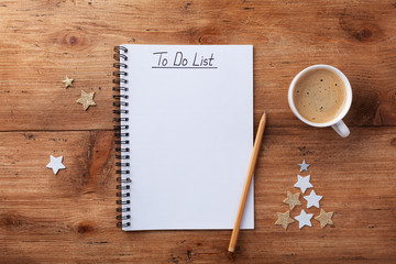 Cup of coffee, stars confetti and notebook with to do list on wooden table top view, Christmas...
