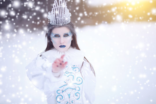 Ice queen with crown in winter landscape