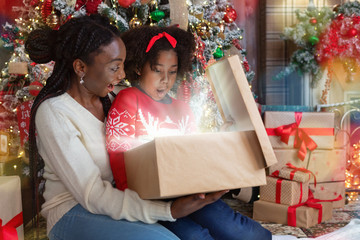 African american mom and daughter opening shining Christmas gift box