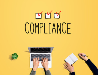 Compliance concept with people working together with laptop and notebook