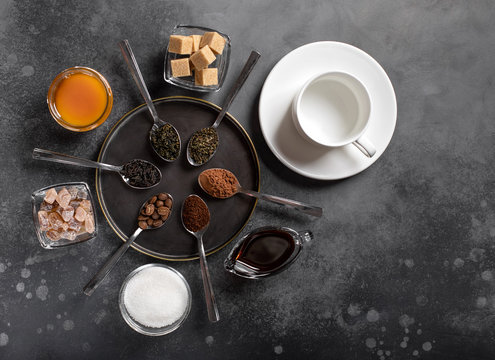 various types of tea (black, green, herbal), coffee (ground, beans, cocoa), sweeteners (sugar, honey, date syrup) and a white empty cup. dark background, top view
