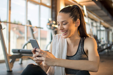 Beautiful sporty woman using phone after sports training at gym