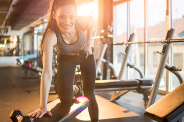Beautiful fit young woman lifting weights on exercise bench at gym