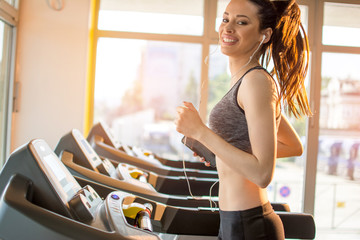 Sportswoman running on treadmill machine at gym