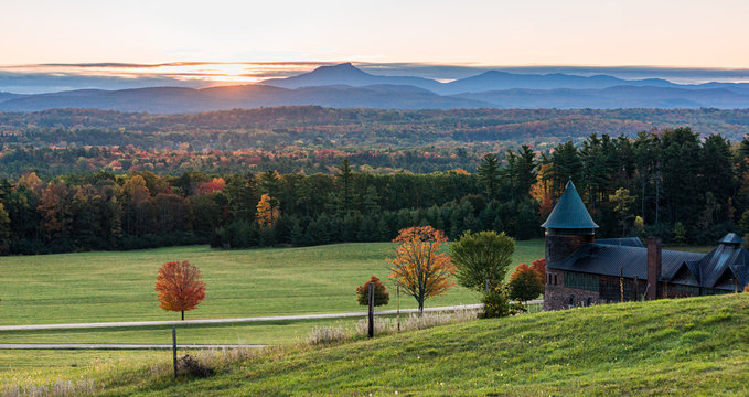 rising sun lights up  Camels Hump Mountain and the Champlain Valley  at Shelburne Farms  historic Barn