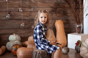 adorable little girl holding pumpkin on wooden background Wall mural