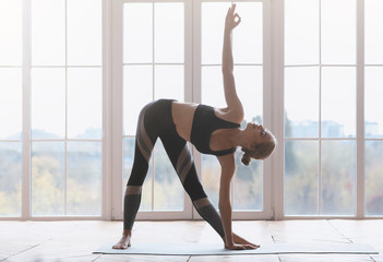 Sporty young woman making triangle yoga pose at studio Wall mural