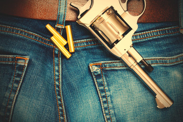 silvery revolver with cartridges on old blue jeans