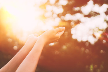 Woman open hand up to sunset sky and green blur leaf bokeh sun light abstract background.