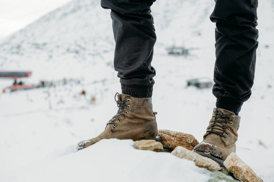 Feet in boots on a background of snowy mountains after a long walk