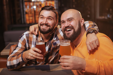 Happy bearded man enjoying drinking beer with his best friend. Male friends hugging, holding up their beer glasses, celebrating at the bar