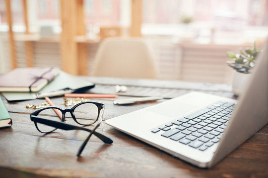 Background image of business office with laptop and supplies on wooden desk, focus on black hard rim glasses in foreground, copy space