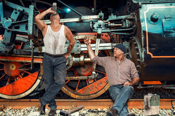 Two mechanics repair an old steam locomotive in a depot