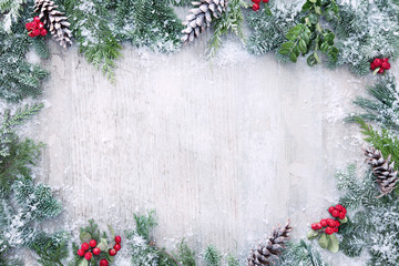 Christmas and New Year background with fir branches and snowfall on wooden white board