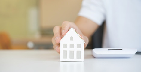 close up on man hand touching home's model on the table for loan mortgage and refinance plan , people lifestyle concept