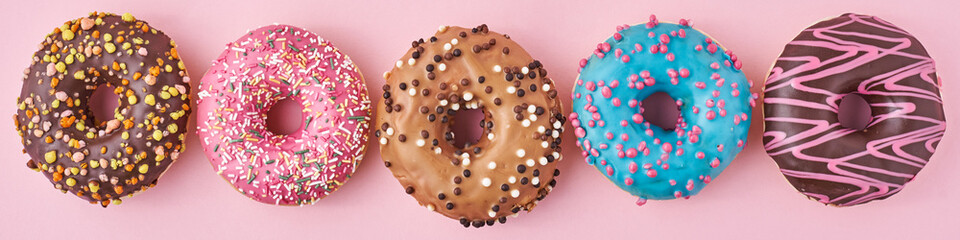 Different types of a colorful donats decorated sprinkles and icing on blue background, long banner Fototapete