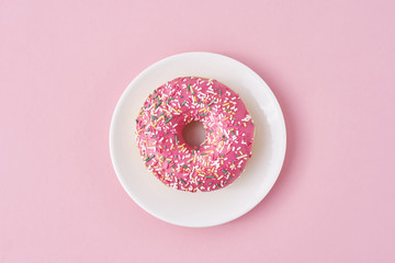 donat decorated sprinkles and icing in white plate on a pink background. Creative and minimalis food concept, top view flat lay