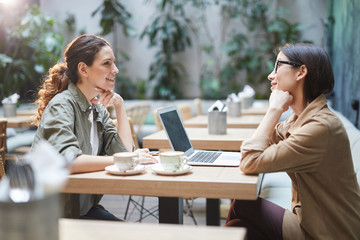 Side view portrait of two modern young women sitting at table in cafe while discussing business during meeting on outdoor patio, copy space