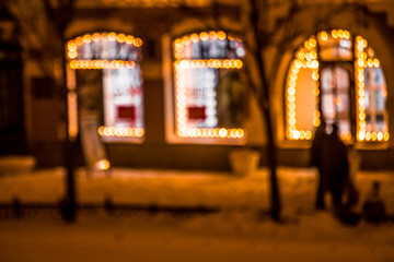 Defocused view of the city street with windows framed with Christmas lights. Night time. Pedestrians walking on the sidewalk Fotomurales