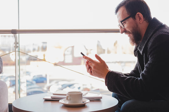 Smiling person with a phone at public place sits against the window. Concept of personal emotions at a crowded urban place: happy male person at a coffee shop with a smartphone in his hands