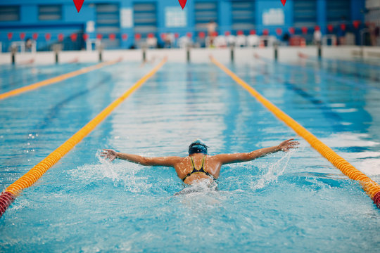 Young woman swimmer swims in swimming pool