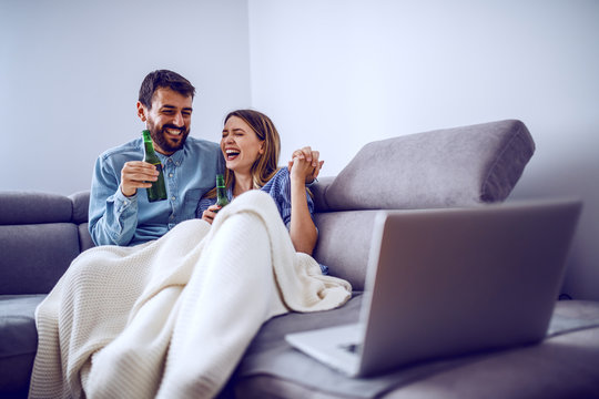 Cute cheerful caucasian couple covered with blanket sitting on sofa in living room, laughing, drinking beer and watching movie over laptop.